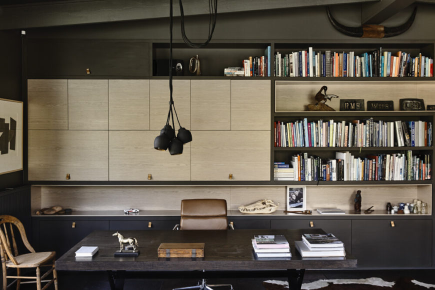 A home office was an important part of the design, a space rife with sleek cabinetry and shelving, centered on a large dark wood desk. The appearance of light toned wood offers a slight break from the prevailing style.