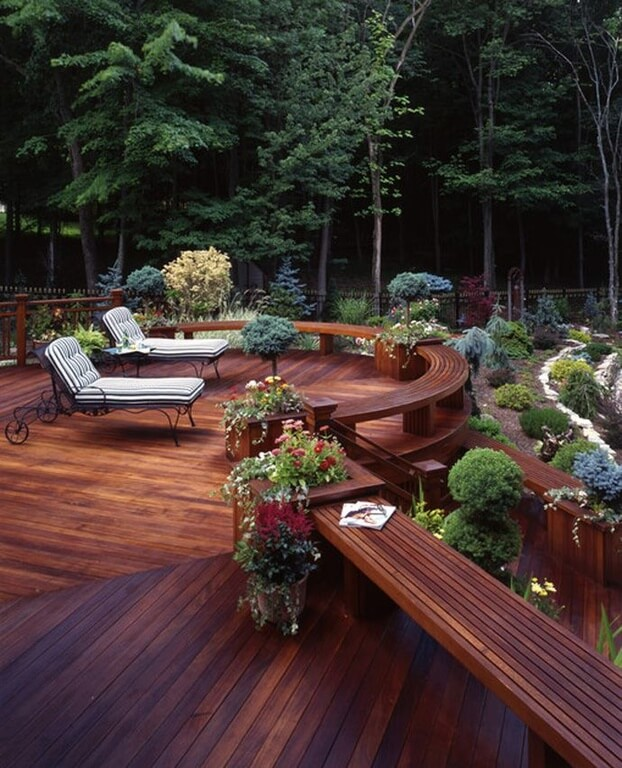 Rounded patio area with benches over looking a well landscaped garden area.