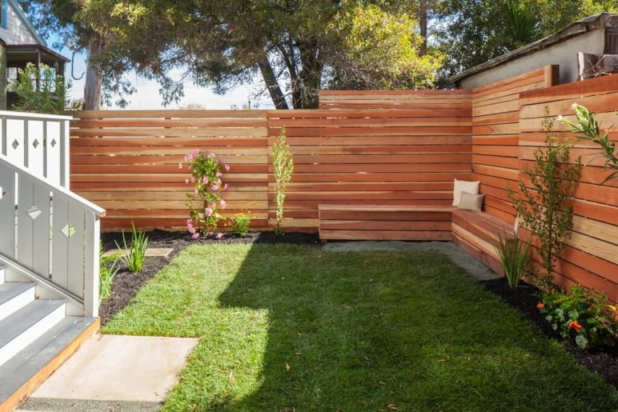 A horizontal slatted privacy fence of wood.