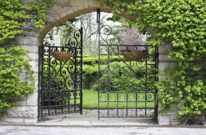 Iron gates pair well with brick walls covered in vines. This is a classic and elegant look that calls to a high class aesthetic. The curved lines in the iron gate are reflected in the natural curves of the vines.