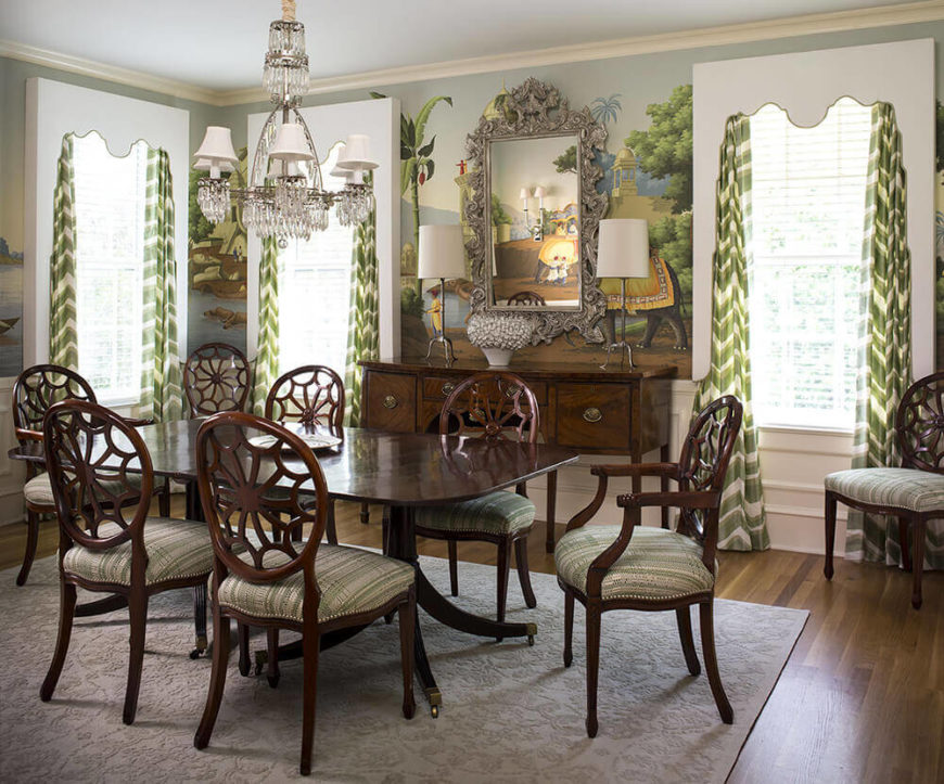 The dining room centers on an incredible rich wood dining table and matching chair set, with intricate carved backs and nailhead trim cushioning. The green and white curtains here complement the wall mural.