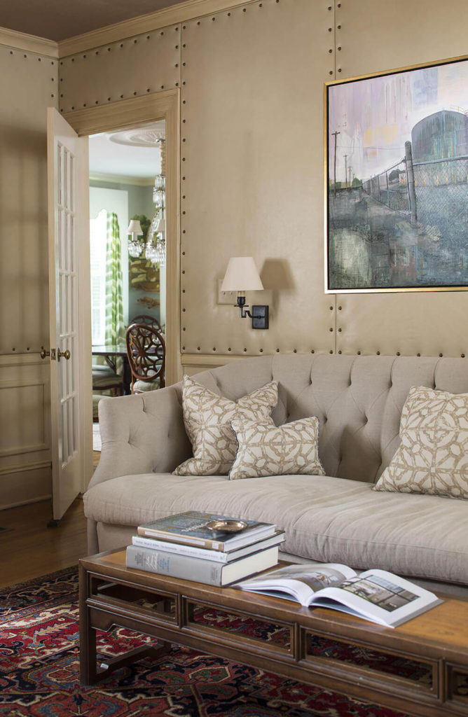 Here's a smaller family room space within the home, features more subtle colors over an interesting set of materials, including nailhead trimmed, upholstered wall panels. The neutral palette hosts elegantly crafted furniture.