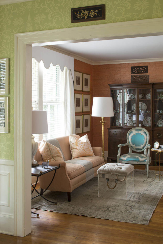 Pulling back from the living room into the foyer, we see that the space is absolutely flush with intriguing hybrid style details, like the button tufted ottoman crafted over an acrylic cube. The hardwood flooring anchors everything in a traditional tone.