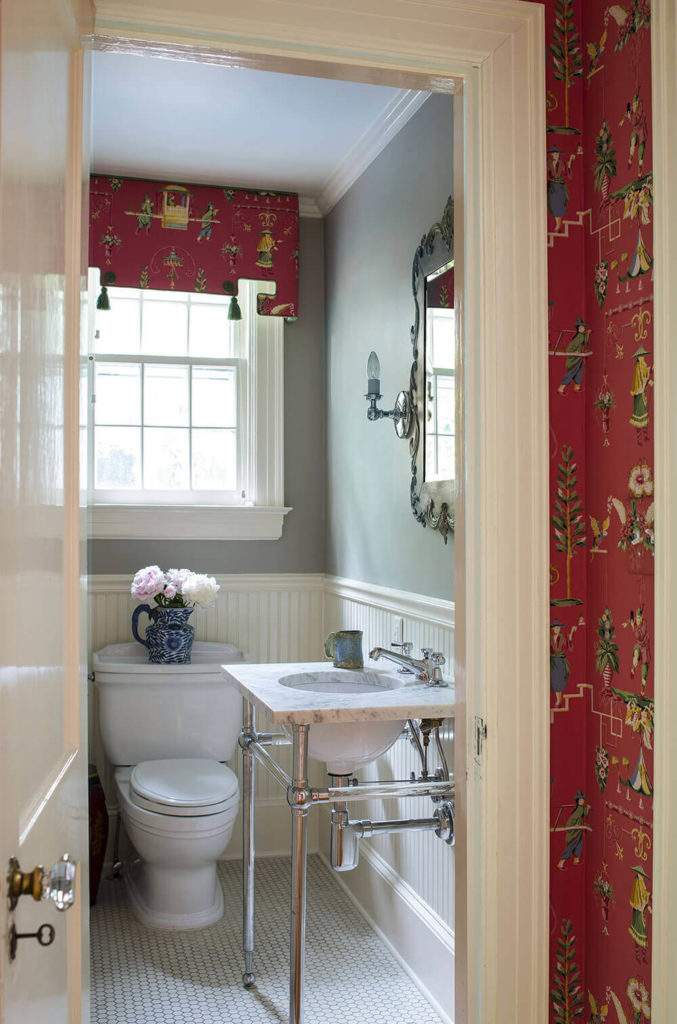 The bathroom offers another take on the unique mixture of traditional and modern, with a marble topped, chrome framed vanity and ornate mirror standing over a micro tile floor.