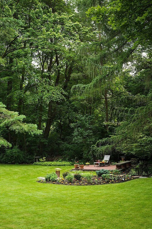 Here is a great back yard with a variety of trees lining the manicured lawn. The trees around this yard provide nice privacy and create a thick forest feel that can make you feel at home and in the wild at the same time.