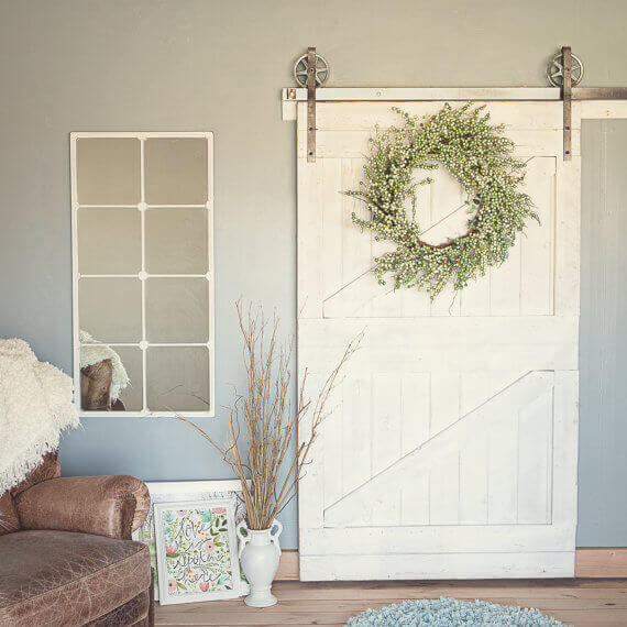 A pure white barn door with industrial metal hardware is the perfect addition to a shabby-chic room aesthetic.