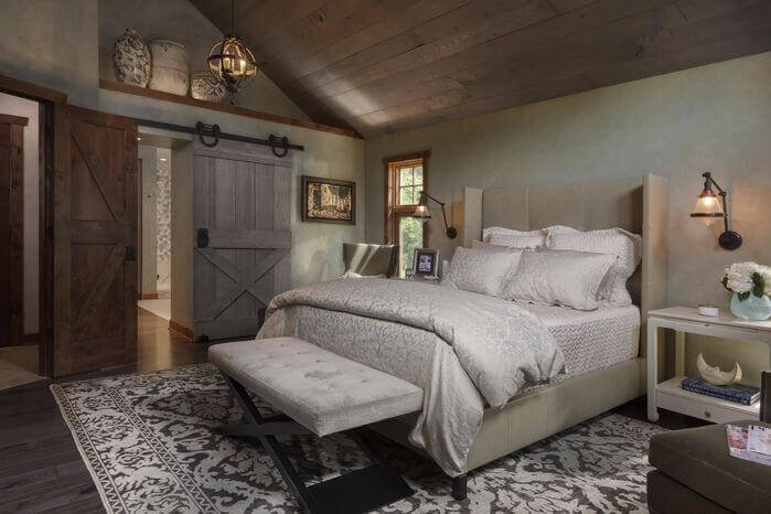While much of the furniture in this master bedroom is contemporary, the wooden ceiling and rustic sliding barn door adds rustic flavor. The orb-like light fixture is another great touch