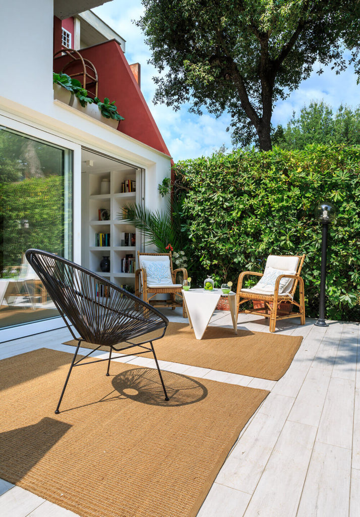 Finally we return to the exquisite backyard patio area, with its flooring that visually extends the living room into the outdoors. This space, wrapped in greenery, is a perfect thematic extension of the home interior.