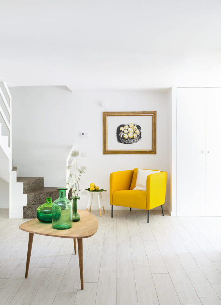 The largely white palette really makes the small instances of color pop. The open floor plan invites plenty of space to move around in, leaving the furniture to stand in spare elegance.
