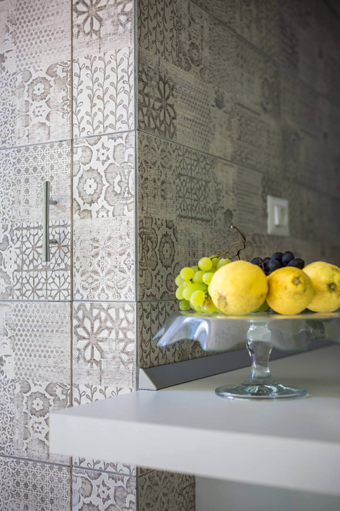 Now we see a closeup look at the subtle floral print wallpaper adorning part of the kitchen wall, lending a bit of textural complexity to the bright, minimalist space.