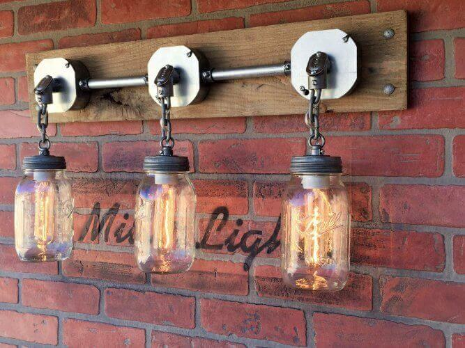 This mason jar wall sconce features three lights attached to the base. Buyers may customize the number of chain links if needed. The sconce uses 3 tubular 25 watt light bulbs, which perfectly fit the mason jars. The fixture is meant to be hard wired to the wall, with no visible wires, allowing for control with a light switch.