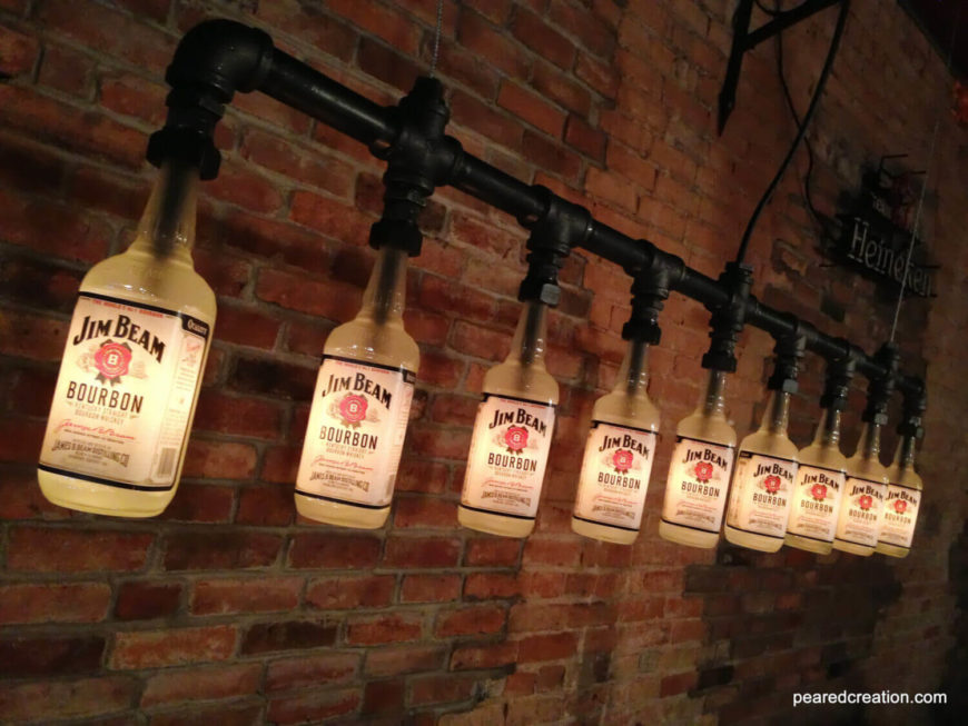 "This lengthy industrial chandelier re-purposes empty Jim Beam Bourbon bottles and was featured on the ""Man Cave"" show. The light gives off a warm ambient glow using low wattage bulbs. The light fixture can be customized with different bottles, so you can feature your favorite brand!"