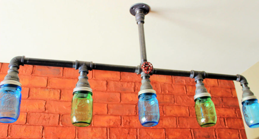 This hanging bar chandelier features blue and green mason jars as the bulb covers. The piece is handcrafted using black pipe, and clear mason jars may be substituted for the colored jars. The light can also be made with or without the red faucet. The light will be hardwired into the wall for power, or it can be designed with a two-pronged plug for a wall outlet.