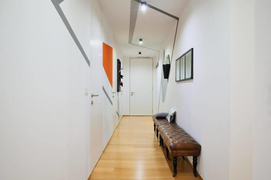 The lengthy hallway is punctuated by sharp, geometric decals on the walls and ceiling, spiking the white palette with sharp edged style. Subtle bursts of color help define this area.