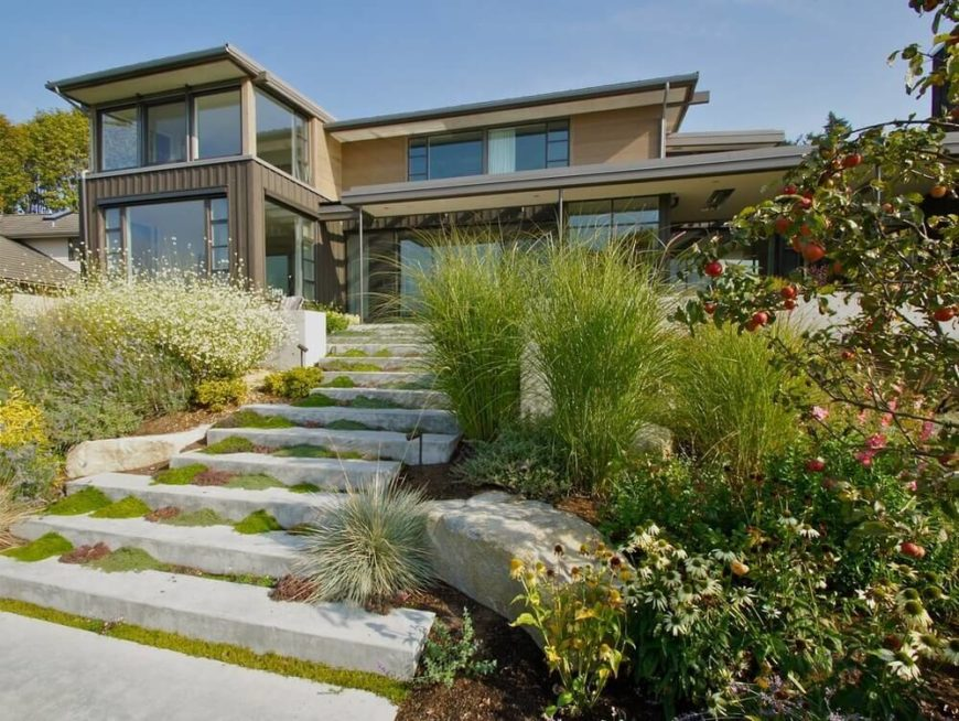 This yard is on a slope and has a great stone and rock landscaping layout. Tall grasses are perfect for accentuating and bringing out the layout of the rock garden.