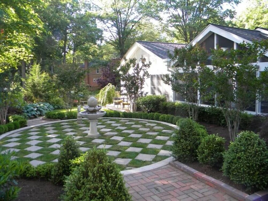 This yard has a great section that includes grass. The grass is in a checkerboard pattern with contrasting stone slabs. This use of grass is very creative and builds visual interest.