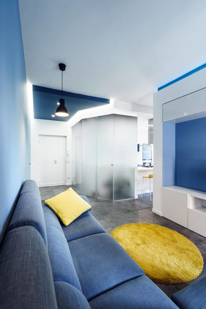 "As seen in the top featured image, the central open space of this apartment is awash in deep blue tones, while a sprinkling of yellow makes for stunning contrast. At center, we can see the frosted glass ""prism."""