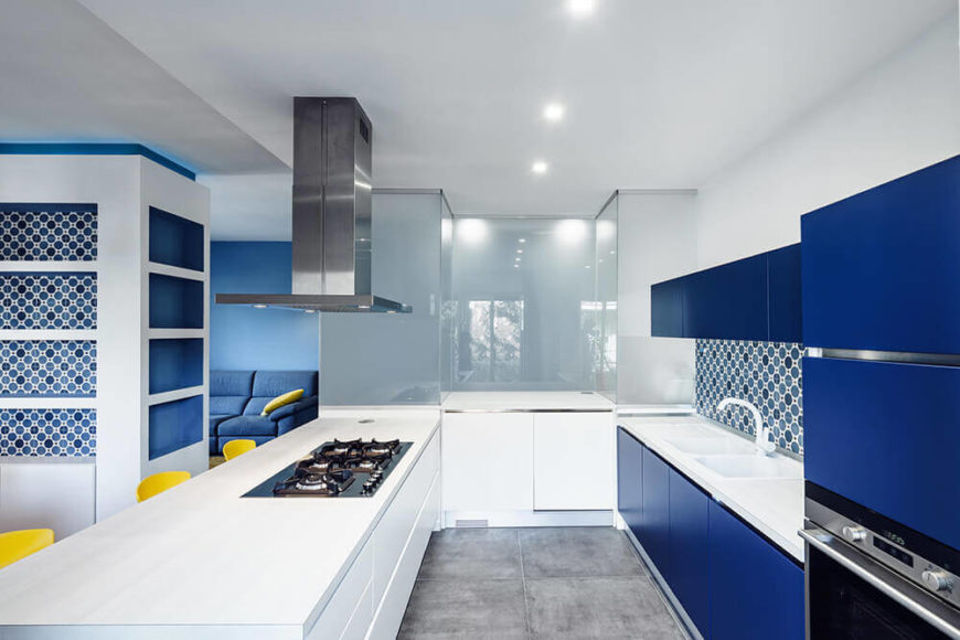Turned full to reveal the rest of the kitchen, we see bold blue cabinetry that connects the area visually to the rest of the open plan space. A unique tile backsplash adds texture and complexity to the look.