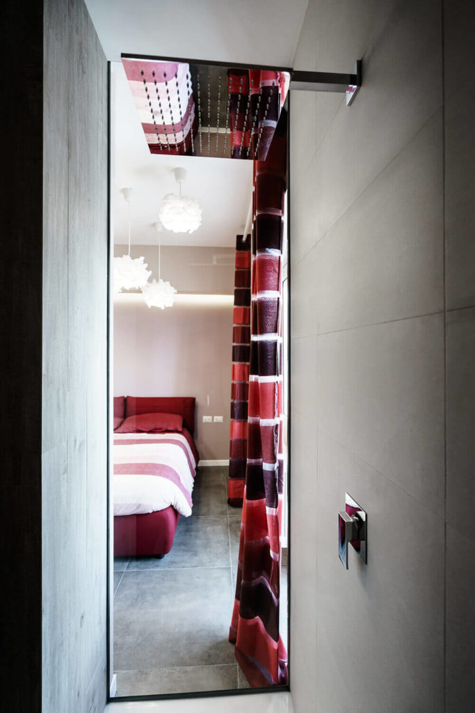 From inside the sleek, minimalist shower, we can see the bedroom awash in sunlight, courtesy of the large window and all-glass balcony access door.