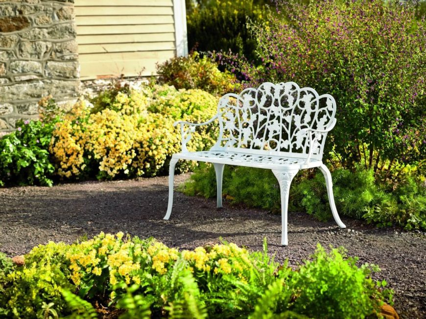 This lovely white garden bench has an intricate and eye catching design. Benches with a design like this can match the natural lines of the plants while allowing the bright colors to contrast with the greens.