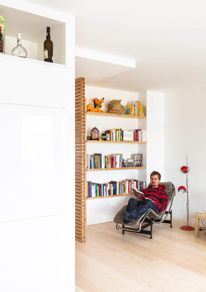 Seen from the dining room, the dividing wall reveals a large set of bookshelves built into the wall, with more rich birch adding contrast and color to the space. A single Scandinavian lounge chair completes the cozy library look.