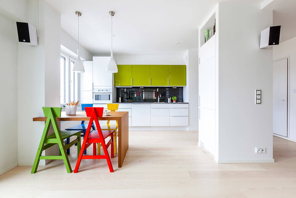 Multi-colored stylish chairs sit at a wooden dining table fixed to the white wall in this minimalist kitchen. It has green and white cabinetry with a glossy black backsplash tile in the middle.