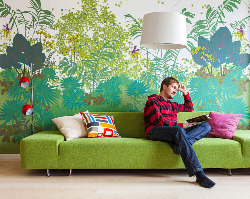 Here we see the bright colors blooming on the opposite end of the open plan area, with the boldly modern green sofa backed against an intricately painted jungle backdrop. An arc lamp and steel-and-red floor lamp complement the space.