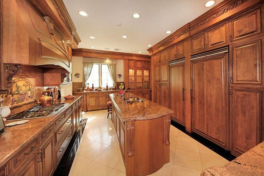 This Mediterranean kitchen is decked out with a great deal of rich wood tones and ornamentation. With a tile floor backdrop the rich wood tones create a very rustic and warm space.