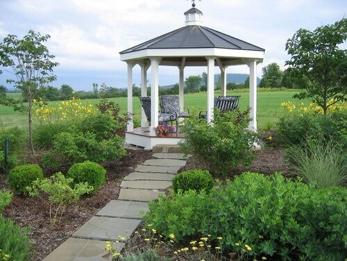 This simple gazebo at the end of a path is perfect for two people to hang out and enjoy the cool breeze on a warm day. It is a lovely spot where anyone would be lucky to get away to.