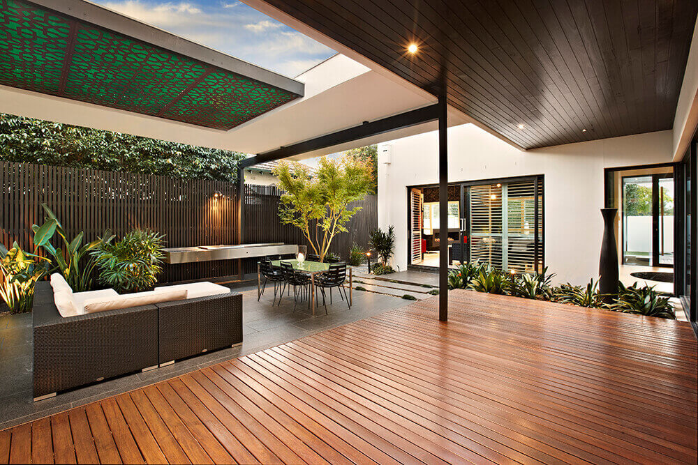 This home features a modish outdoor kitchen with a floating vanity counter, small dining table set and a patio area.