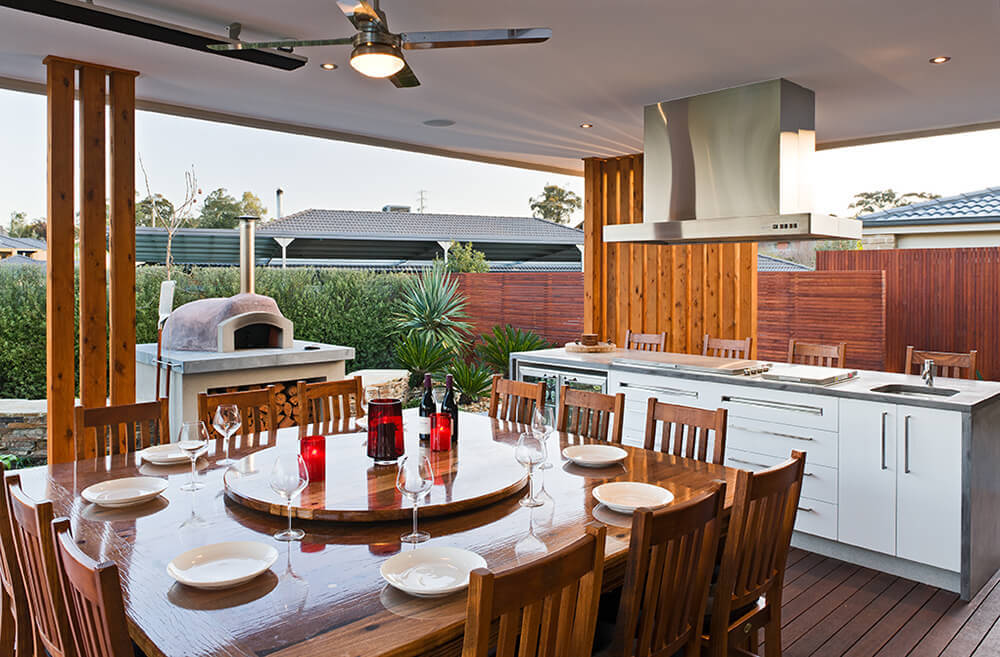 Outdoor kitchen with a long bar counter along with a huge dining table set set on the home's deck.