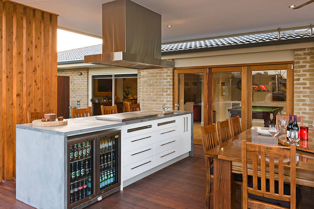 This kitchen offers a modern bar counter with fridge full of beers. There's a wooden dining table set near the counter.