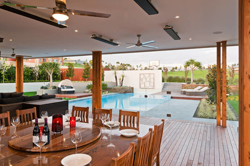 The view from this space is spectacular. We can see the pool and surrounding patio segments, as well as a wealth of plant life surrounding the property.