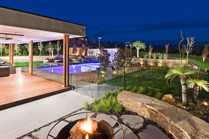 Off to the side of the sheltered patio area, we see the raised fire pit space with surrounding flagstone rock wall. The complex, layered landscape design can be fully appreciated here in its various stages.