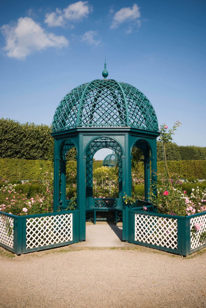 This gazebo has attached matching fences that circle around garden areas, making this gazebo an integral part of the garden's design.
