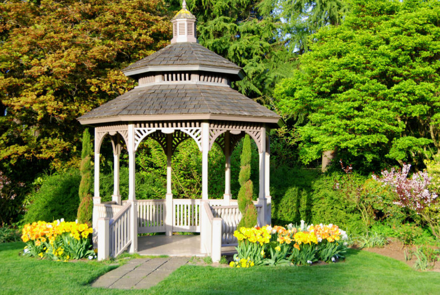 This bright and welcoming gazebo is surrounded by hedges and bright yellow flowers. This space is a wonderful focus for a landscape or garden.