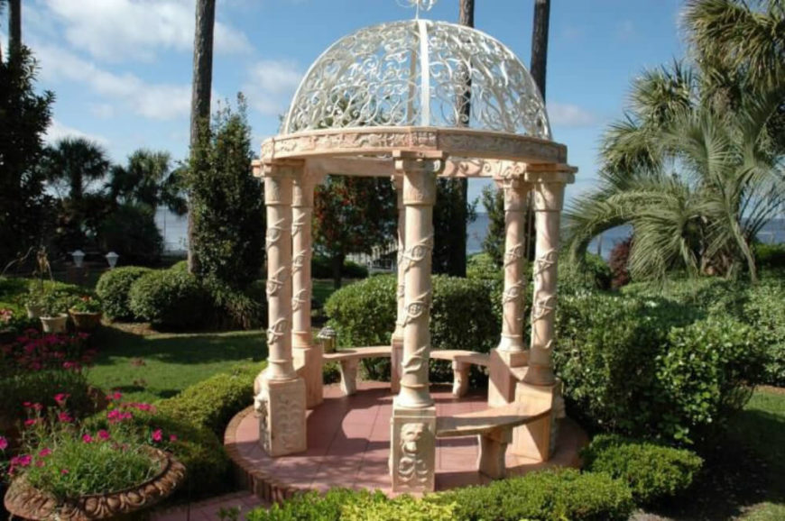 This stylish and decorative gazebo sits among a plethora of different plants, mostly hedges. Well trimmed hedges are perfect for developing a manicured upscale look and this gazebo works well with that appeal.