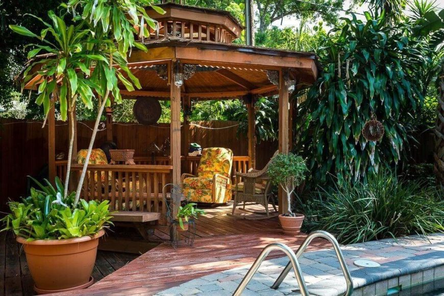 This gazebo sits on the side of a pool, surrounded by lush plants and filled with lovely furniture. This is a wonderfully shady spot to gather, read, or simply enjoy a warm summer day by the water.