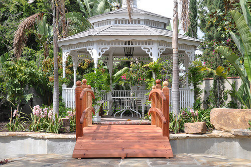 Across this bridge, on the other side of the water feature and among the hanging plants, is an elegant and high end gazebo. This gazebo is a wonderful example of how well a gazebo can fit in with landscaping and yard design.