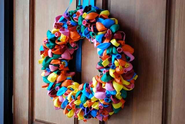 Have some extra balloons hanging around after a birthday party? You can use those as the basis of this colorful and festive wreath for your front door!