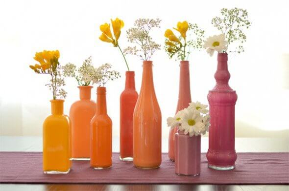 This is a classic, easy DIY project that transforms old glass bottles into colorful vases!