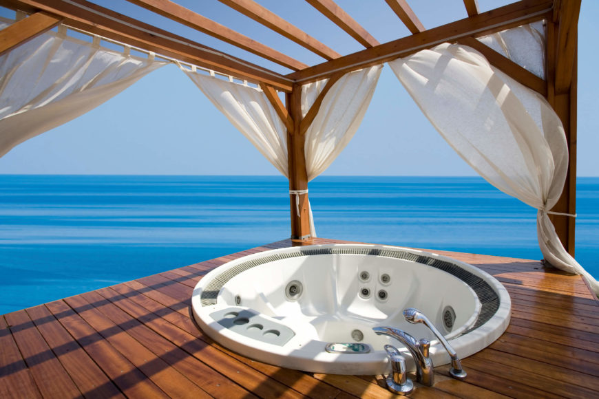this gazebo and deck on the water is equipped with a hot tub as well as
