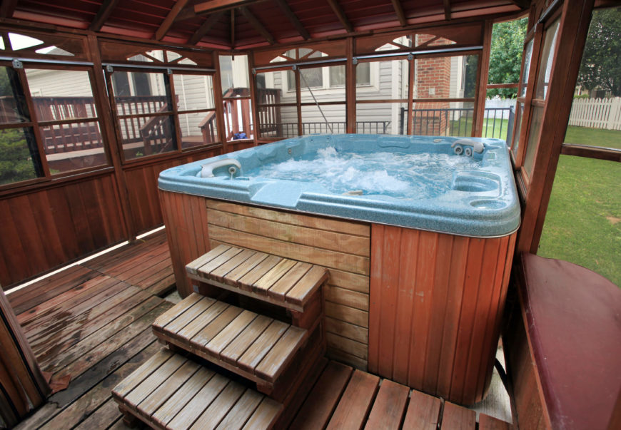 This above ground hot tub is built into the deck and topped with a walled gazebo. Creating a private and intimate space for your hot tub makes the area welcoming and cozy.