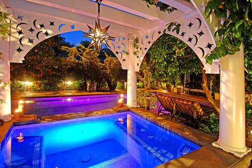 A gazebo is a great way to hang lighting fixtures in areas that need more lighting. This hot tub is enhanced by the chandelier above it.