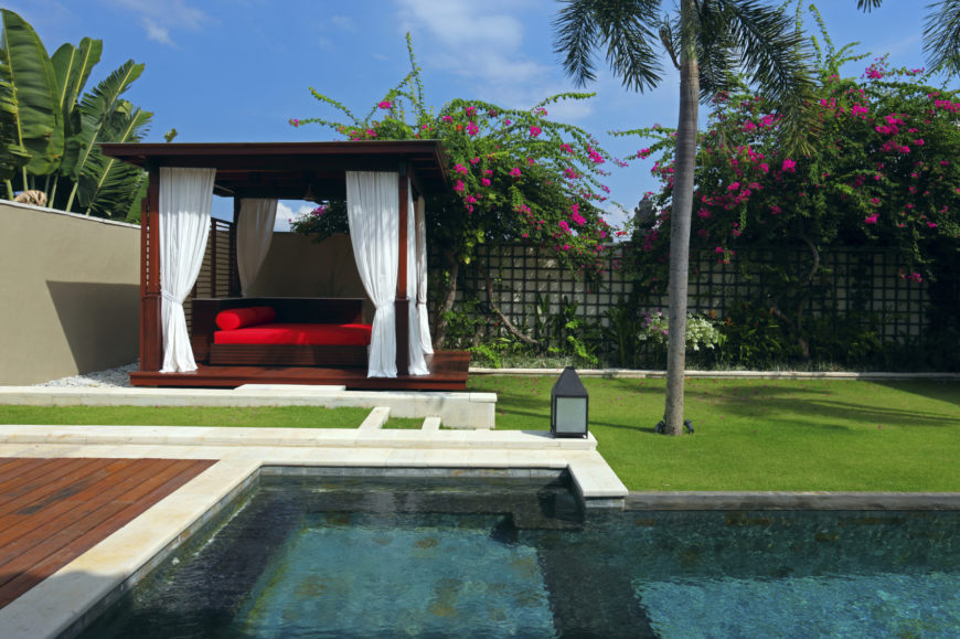 This stunning and luxurious gazebo is equipped with heavy white curtains and an enticing deep red sofa. You will feel like royalty lounging here after a nice soothing swim.