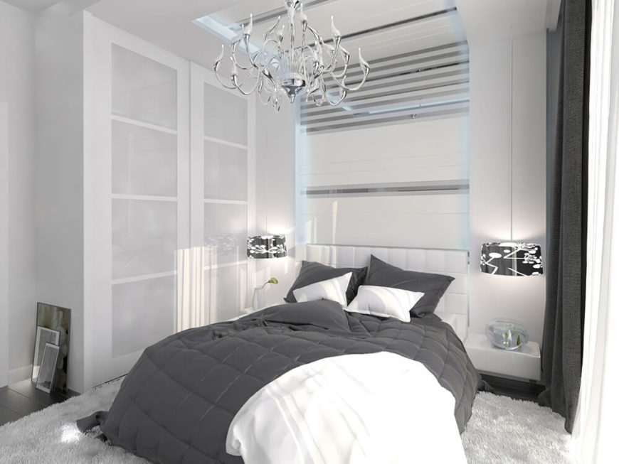This bedroom accents its bold white modernism with a traditionally styled, glossy chrome chandelier. White walls and storage contrasts deeply with dark grey bedding, drapes, and flooring.