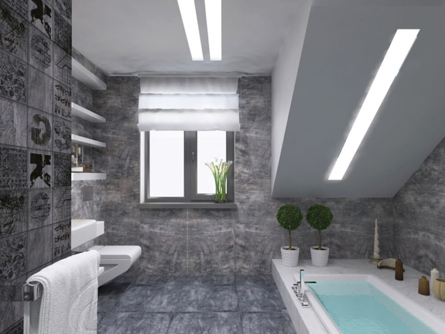 The master bath is awash in rich grey tile from floor to ceiling, with unique builtin shelving and a large sunken soaking tub.
