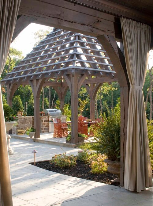 The tall pyramid-shaped gazebo lets light through to the grill and patio area, but still sections off the area as different from the rest of the backyard.