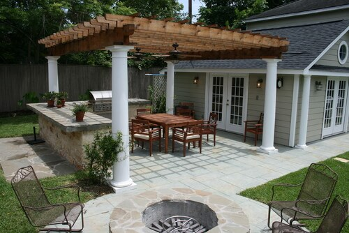 This grill fits neatly into the stone and concrete preparation area, which is covered by a pergola.