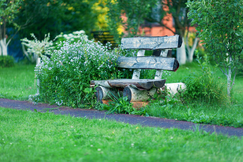 Logs cut, piled and nailed into a garden bench sunk within thick green grass and wildflowers.